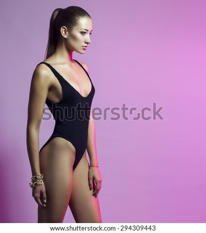 High heels and fitness concept. Fashion portrait of beautiful young model with long hair in trendy black swimsuit, cool shoes posing over pink background. Perfect body. Studio shot - stock photo