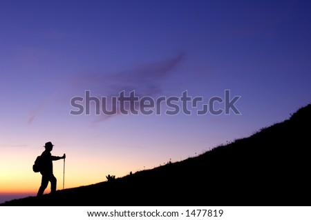 High in the mountains a walker climbs a ridge, silhouetted in the pre-dawn light. - stock photo