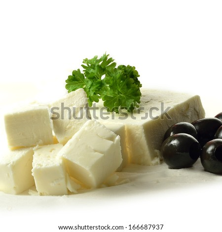 High key image of a block of fresh Feta cheese with black olives and parsley garnish on grease-proof paper against a white background. Copy space. - stock photo