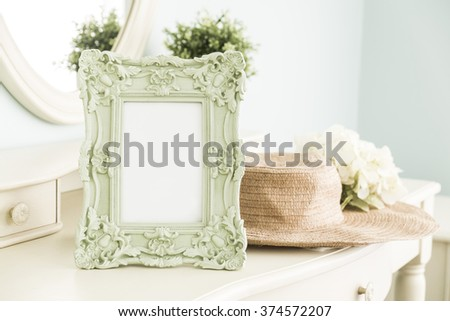 High key photo of Vintage frame on table with hat in front of the mirror, bedroom scene - stock photo