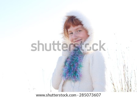 high key portrait image of young red haired girl wearing a white woollen knitted jacket with fur trimmed hood against a wintry white sky, naturally lit at a beach in New Zealand  - stock photo