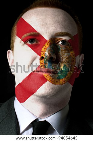 High key portrait of a serious businessman or politician whose face is painted in american state of west florida flag - stock photo