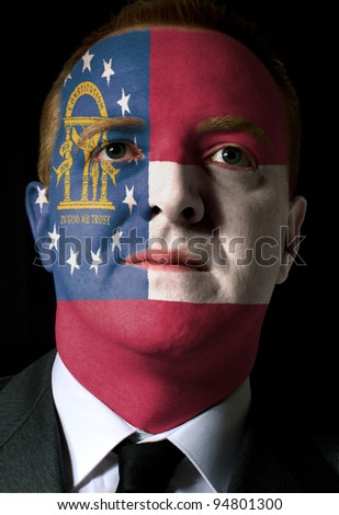 High key portrait of a serious businessman or politician whose face is painted in american state of georgia flag - stock photo
