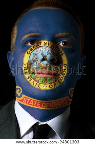 High key portrait of a serious businessman or politician whose face is painted in american state of idaho flag - stock photo