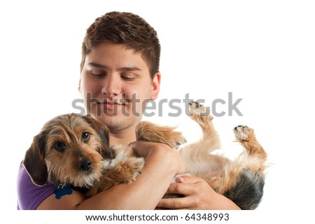 High key portrait of a young man holding a cute mixed breed borkie dog isolated over white. Shallow depth of field with focus on the mans face. - stock photo