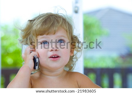 High key portrait of young baby with mobile phone - stock photo