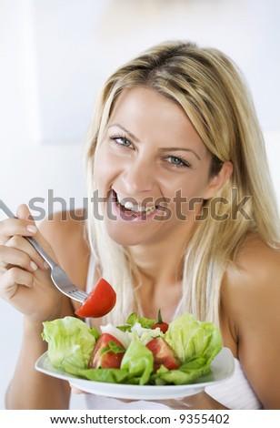high-key portrait smiling female eating her salad - stock photo