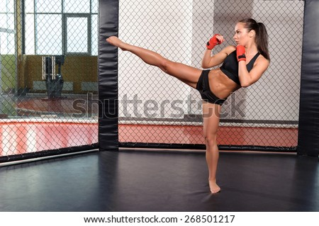 High kick. Strong sportswoman shows her high kick in a boxing ring - stock photo