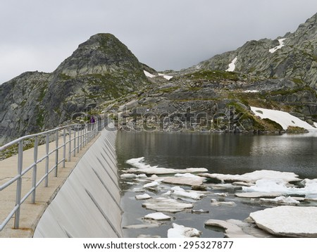High mountain dam wall in a cloudy day - stock photo