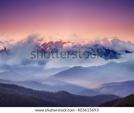 High mountain ridge in the clouds during sunrise. Beautiful panoramic landscape - stock photo