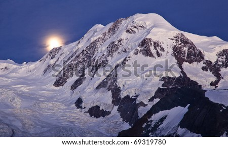 High mountain scenery with Liskamm peak and the moon at night - stock photo