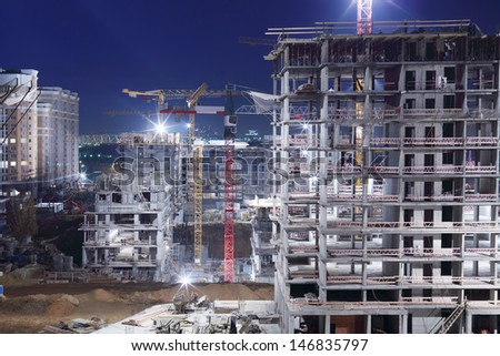 High multi-storey buildings under construction and cranes at night. - stock photo