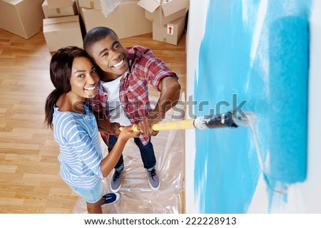 high overhead view of young black couple painting wall with roller in new house - stock photo