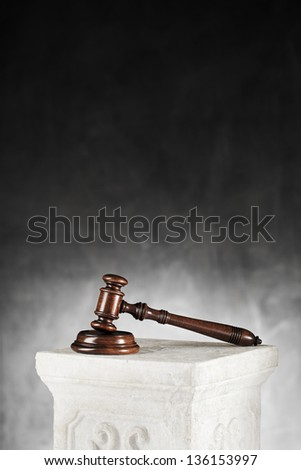 High quality mahogany gavel with sound block on a plaster column. - stock photo