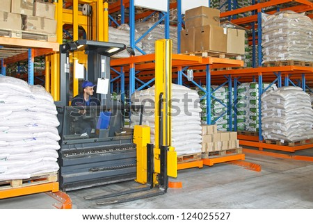 High rack stacker forklift between rows in warehouse - stock photo