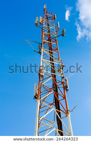 High red and white antenna mast on blue sky background - stock photo
