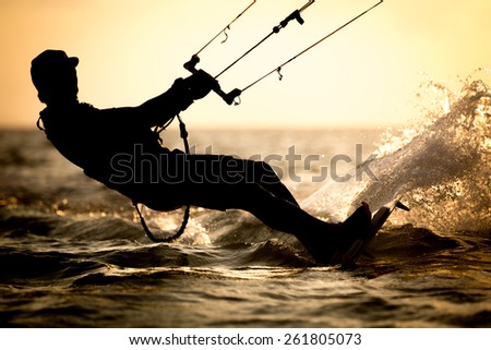 High resolution and superb quality photo of a rider doing kitesurfing tricks, with backlit sunset - stock photo