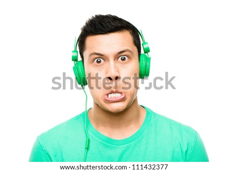 High resolution portrait crazy asian man pulling funny faces wearing headphones isolated on clean white background - stock photo