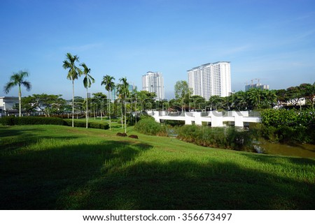 High rise apartment with garden in surrounding. Daylight with long shadow and blue sky - stock photo