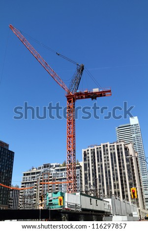 high-rise building crane on top of building construction site - stock photo