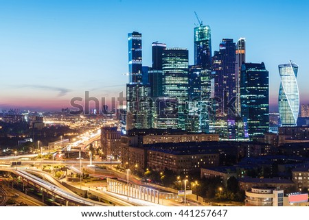 high-rise buildings and transport metropolis, traffic and blurry lights of cars on multi-lane highways and road junction at night in Moscow - stock photo