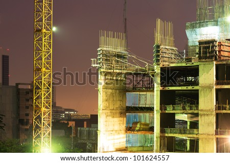High rise concrete building construction with a yellow crane - stock photo