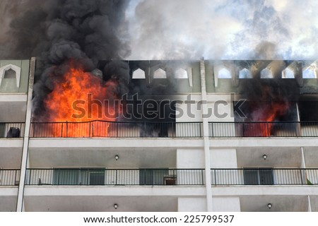 High rise condominium or apartment fire with flames coming out the windows.  - stock photo