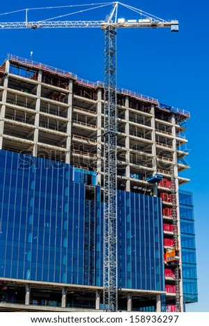 High-Rise Construction Job.  High altitude building assembly.  Concrete, steel, glass, and man in concert. - stock photo