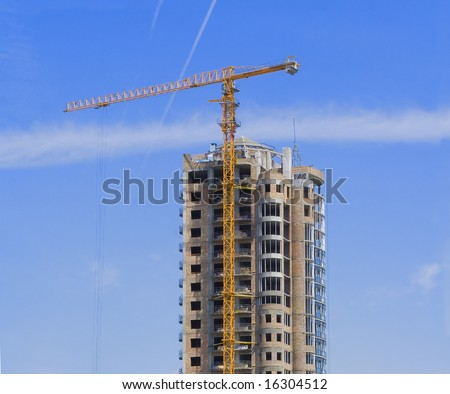 High rise construction site with crane against a bright blue sky. - stock photo