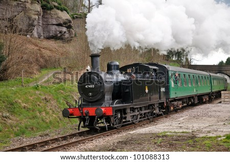 HIGH ROCKS, ENGLAND - APRIL 15: A jinty steam locomotive passes the High Rocks tourist location en route to Tunbridge during the Spa Valley Railway spring steam gala on April 15, 2012 at High Rocks - stock photo