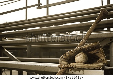 High school baseball practice with ball in glove and bat on bleachers.   - stock photo