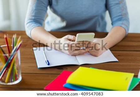high school, education, people and learning concept - close up of young student or woman with smartphone and book writing to notebook at home - stock photo