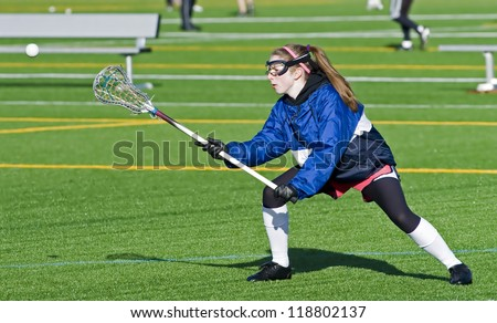 High school girl lacrosse player reaches out to catch the ball. - stock photo