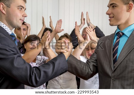 High school graduates shaking hands while happy parents and grandparents applauds on the background  - stock photo