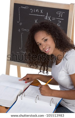 High school or college African-American black female student sitting by the desk at math class. Blackboard with advanced mathematical formals is visible in background - stock photo