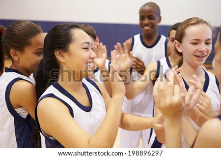 High School Sports Team Celebrating In Gym - stock photo