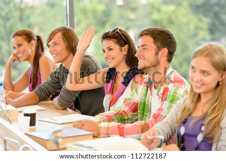 High-school student raising her hand in class lesson teenagers study - stock photo