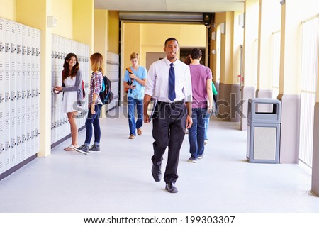 High School Students And Teacher Walking Along Hallway - stock photo