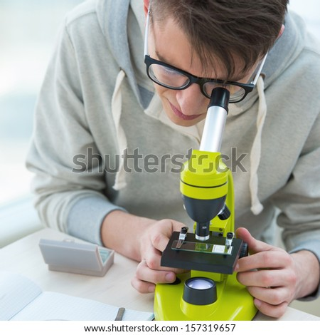 High School students. Handsome guy working at biology classroom: looking through microscope - stock photo