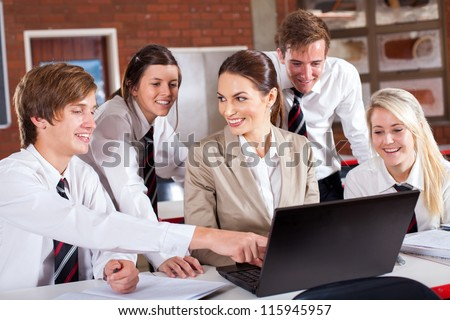 high school teacher and students with laptop in classroom - stock photo