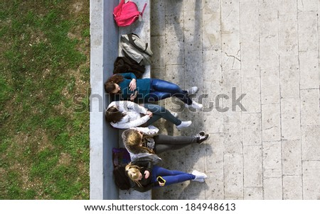 High school teen girls sitting on the bench after school or while on pause or break.  - stock photo
