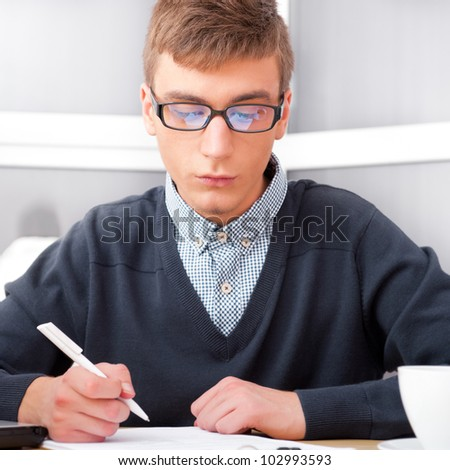 High school - Young male student write notes in classroom - stock photo