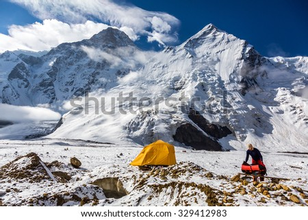 High Snowbound Peaks and Man Packing his Climbing Backpack Staying next to Orange Tent - stock photo