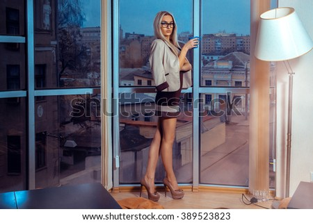 High society blonde woman in glasses with cup of tea by the large window with city views . Business woman drinks tea. City views behind the window in the office. Business concept. - stock photo