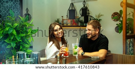 High society people having fun at the bar with cocktails. Beautiful couple smiling. Nightlife concept. - stock photo