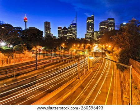 high-speed express crocc-city motorway in Sydney with city CBD skyscrapers in the background at sunset when vehicle headlights are blurred  - stock photo