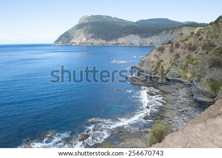 High steep cliff coast on Maria Island, Tasmania, Australia, National Park and World Heritage Site, with ocean and mountain of Bishop and Clerk as background, copy space. - stock photo