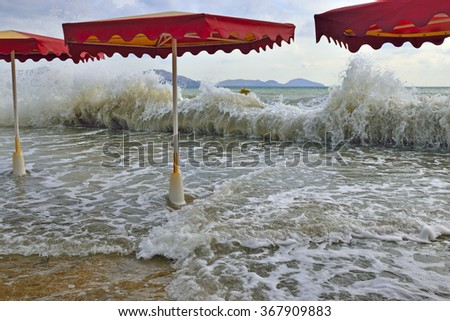 High storm waves rolled on shore and fill the beach with awnings from  the sun. - stock photo