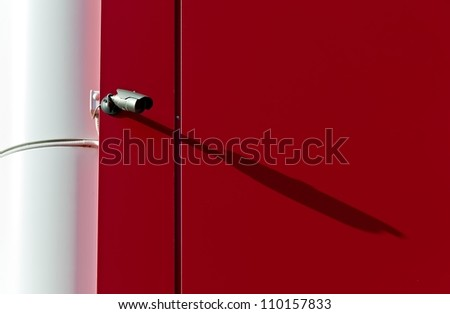 High-tech infrared security camera on the background of a red wall. - stock photo