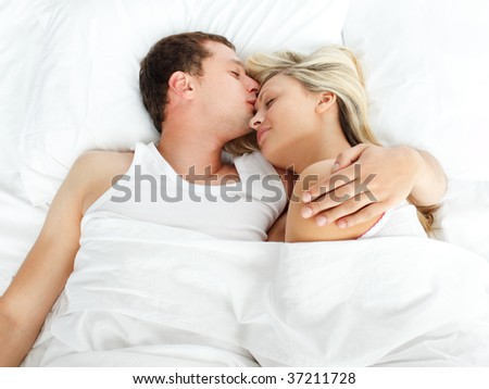 High view of boyfriend kissing her girlfriend in bed - stock photo